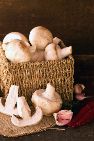 fresh mushroom in a handmade rustic box over a dark wooden background photo