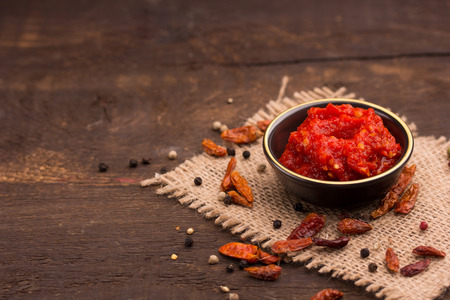 chilli: chilli sauce in a cute little bowl on a wooden table