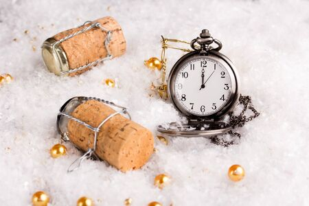o'clock: new years eve concept with champagne cork and a pocket watch showing twelve oclock