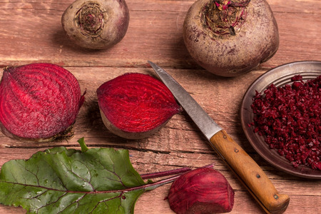 brownish: composition with red beets and knife  on a wooden table Stock Photo