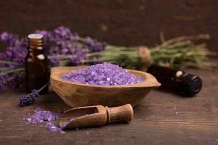 bath essence: lavender flower,essence and bath salt over a wooden table Stock Photo