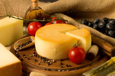 queso: Rueda del queso sobre tabla de cortar de madera Foto de archivo