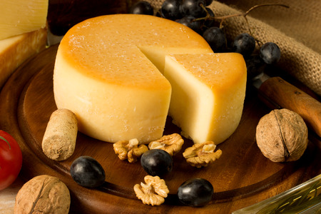 round cheese on a cutting board, with nut and grape