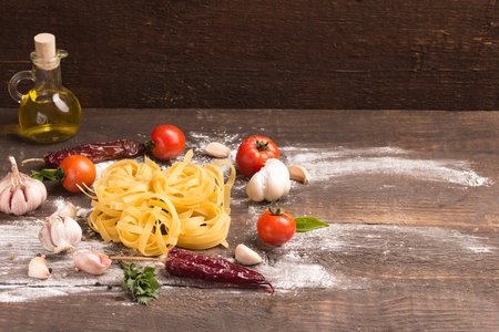 fresh home made pasta with food ingredients over wooden table
