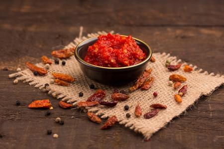 chili sauce on a rustic dark wooden table Standard-Bild