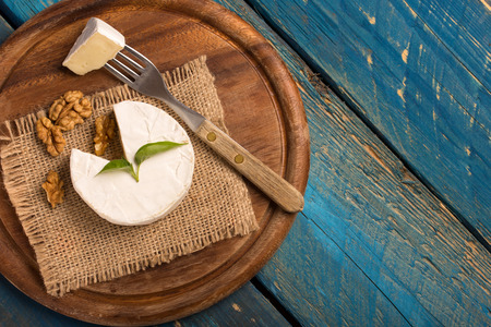 camembert cheese on a cutting board over a blue wooden table