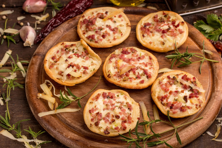 pizza: mini pizzas and food ingredients on a cutting board Stock Photo
