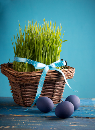 wooden basket: blue easter eggs in a basket, with grass, over wooden background