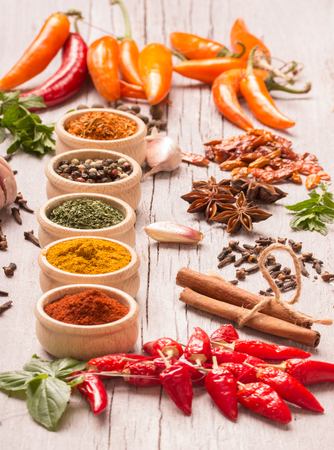 indian spices: vertical composition of colourful spices on wooden table Stock Photo