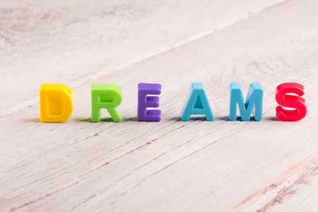 worldwide wish: the word dreams on a white wooden surface Stock Photo