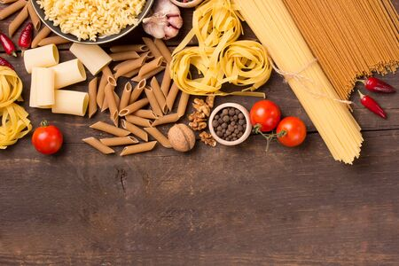 unboiled: various italian pasta with ingredients in rustic style Stock Photo