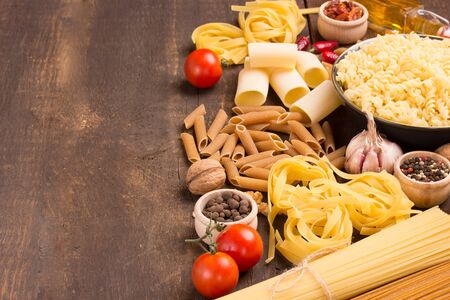 unboiled: italian pastas with food ingredients on wooden table Stock Photo