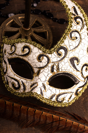 costume ball: carnival mask on dark wooden background
