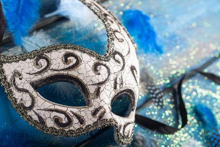 female carnival mask with blue glittering background