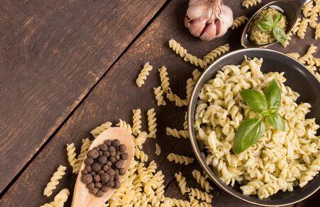 fusilli: fusilli with pesto sauce over wooden background