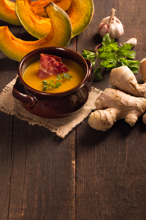 pumpkin soup: pumpkin soup with bacon in a rustic bowl
