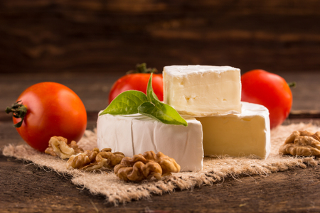 penicillium: camembert cheese with nuts and tomato Stock Photo