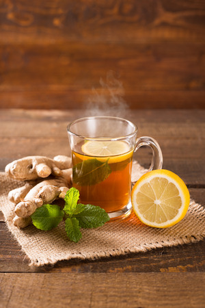 cup of hot ginger tea with mint and lemon