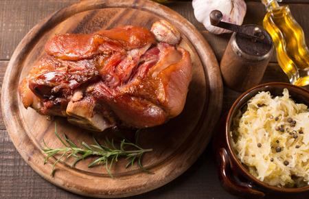 shank: Baked pork shank and sauerkraut on a wooden table. horizontal