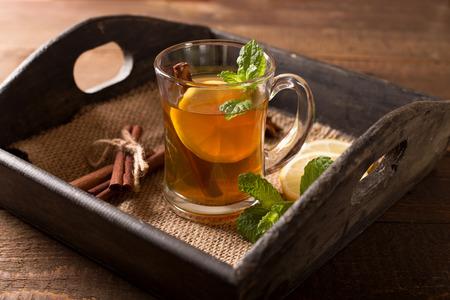 limón: transparent glass of hot tea with lemon,mint and cinnamon