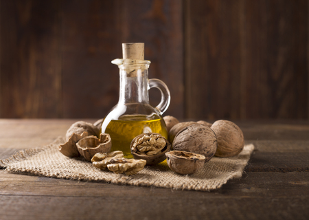 Walnut oil and nuts on wooden table Standard-Bild