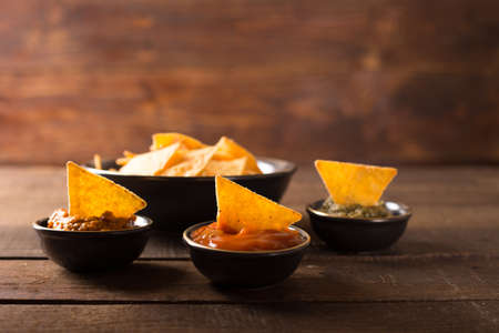 nacho: Mexican nacho chips and various sauces in bowl on wooden background