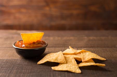 bailar salsa: Nachos mexicanos e inmersión de la salsa en un tazón sobre fondo de madera