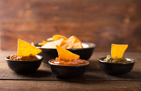 nachos: Mexican nacho chips and various sauces in bowl on wooden background