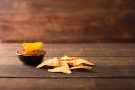 nachos: Mexican nacho chips and salsa dip in bowl on wooden background