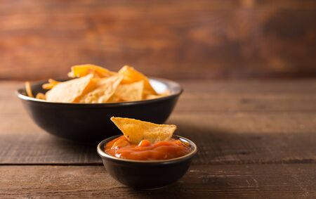 tortilla chips: Mexican nacho chips and salsa dip in bowl on wooden background