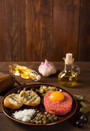 steak tartare: fresh beef tartar with egg, onion, capers, cucumber Stock Photo