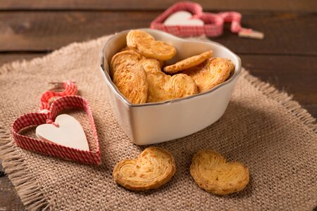 scuits in heart shaped bowl on wooden table Stock Photo
