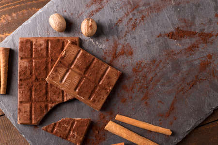 sweet segments: Broken chocolate bar and spices on stone board