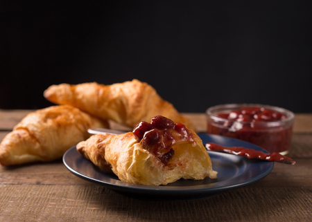 spoted: Homemade  Croissants  with strawberry jam on wooden table