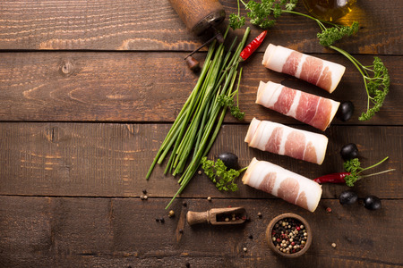 jambon: Delicious sliced bacon on wooden table with herbs Stock Photo