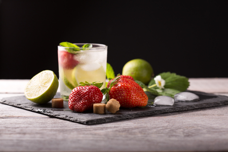 strawberry lime mohito cocktail on a white wooden table