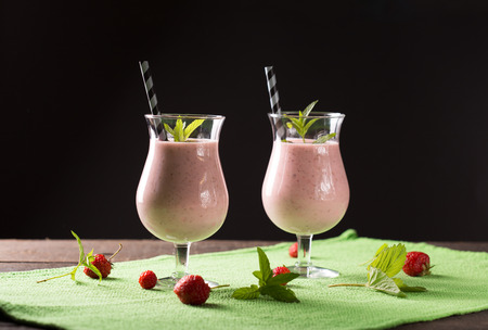 red straw: strawberry smoothie on wooden table
