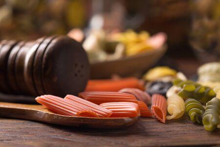 various coloured pasta over wooden background Standard-Bild