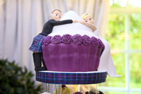 cute bride and groom edible marzipan figures on the top tier of the wedding cake.