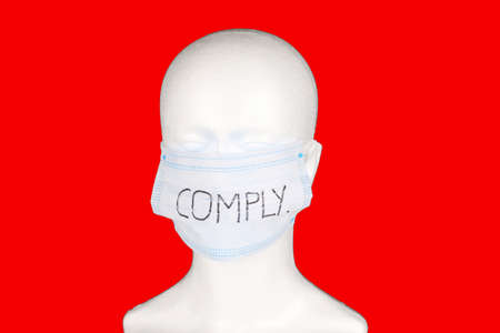 comply written on a face mask placed on a mannequin dummy with red background