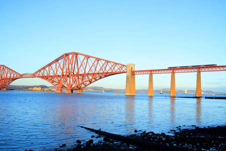 forth road railway bridge with traain passsing over the blue of the river with blue skies above.