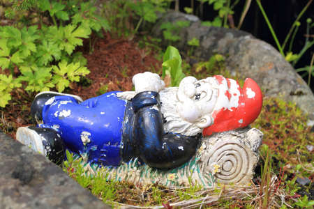 faded gnome with red hat, blue trousers, black top and black shoes lying on a log in the garden.