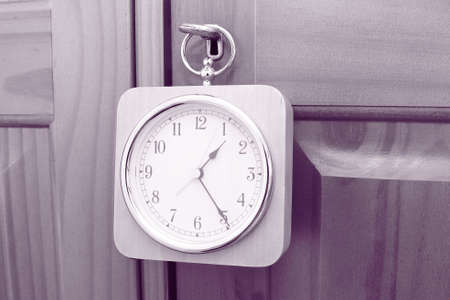 wooden clock hanging on the key of a wooden door with purple coloured filter