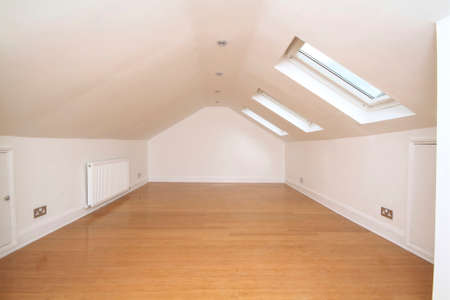 empty attic bedroom with skylight windows Banque d'images