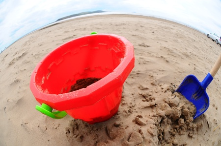 Wide angle close up of a childs bucket and spade on a beach