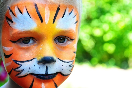 cara pintada: Chico joven y feliz con la cara pintada como un tigre