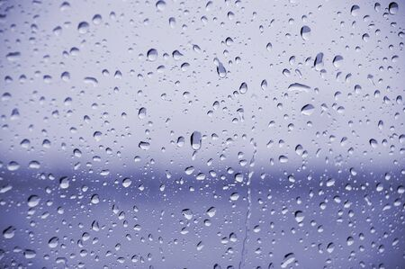 rain drops on window against blue background Stock Photo