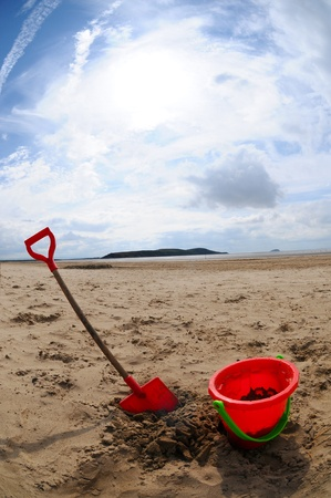 A childs red platic bucket and spade on a beach