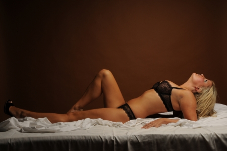 Sexy young woman led on her bed in black lingerie