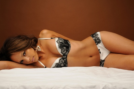 A sexy young woman lying on her bed in lingerie photo